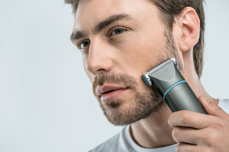 handsome man using electric razor, isolated on grey 免版税图像