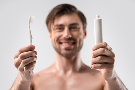 selective focus of man holding toothbrush and toothpaste, isolated on white