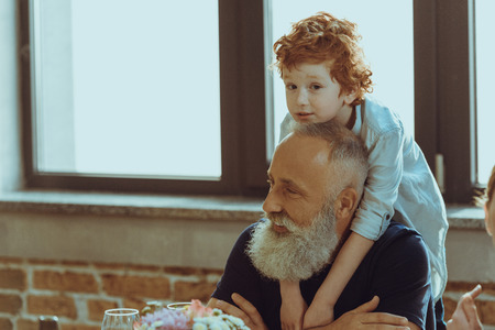portrait of little boy hugging happy grandfather at home 版權商用圖片