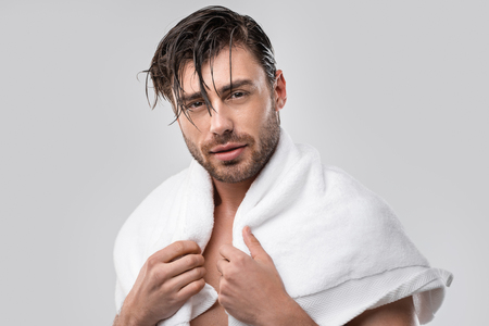 hübscher Mann mit nassen Haaren und Handtuch, isoliert auf grau