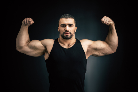 portrait of strong man showing muscles isolated on black