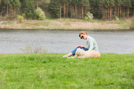 beautiful young woman in sunglasses stroking dog while sitting on green grass near river