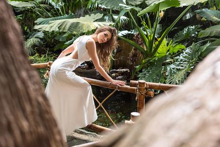 beautiful woman in white dress posing in tropical orangery