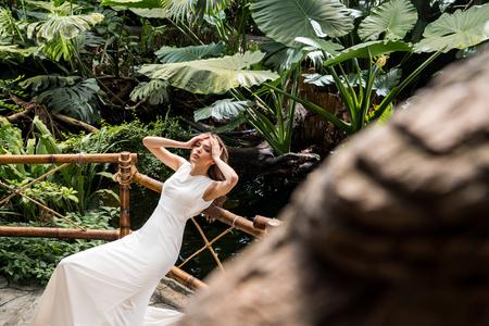 beautiful sensual woman in white dress posing in tropical orangery
