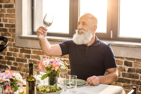 portrait of senior man looking at empty wine glass in hand