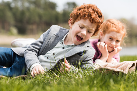 adorable red haired brother and sister lying together on grass