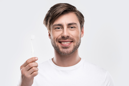 handsome smiling man holding toothbrush, isolated on white Stock Photo