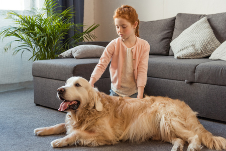 portrait of little girl petting dog while sitting on floor at home