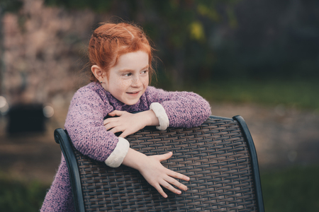 portrait of little girl looking away while standing near chair at backyard Banco de Imagens
