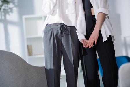 cropped shot of stylish lesbian couple holding hands Stock Photo