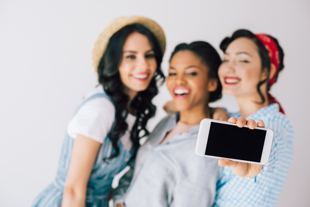 selective focus of multicultural happy women taking selfie on smartphone together isolated on grey