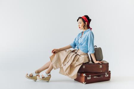 灰色に隔離された荷物の上に座ってレトロな服を着た美しいアジアの女性 写真素材