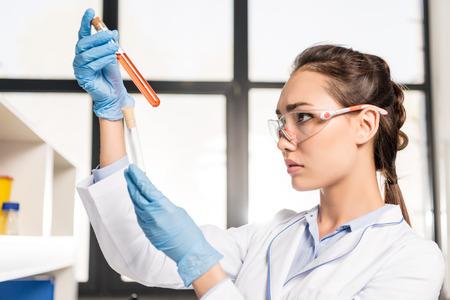 Portrait de jeune scientifique dans des lunettes de protection comparant des tubes à essai dans ses mains