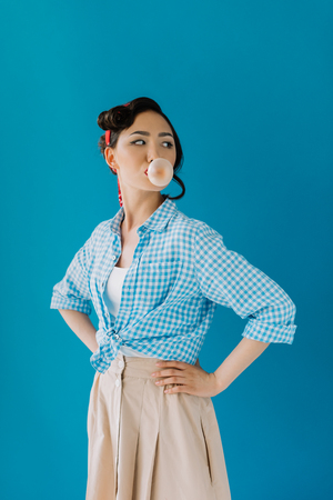 portrait of asian woman in retro clothing standing akimbo and blowing bubble gum isolated on blue