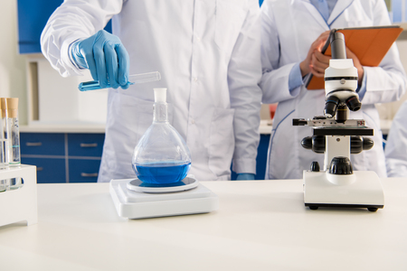 Partial view of medical worker pouring liquid from test tube into flask and weighing it on electronic scales