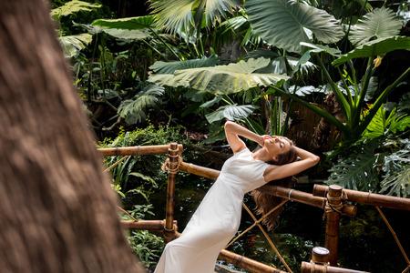 beautiful seductive woman in white dress posing in tropical orangery Stock Photo
