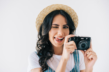 portrait of winking woman with photo camera in hands sticking tongue out isolated on grey 版權商用圖片