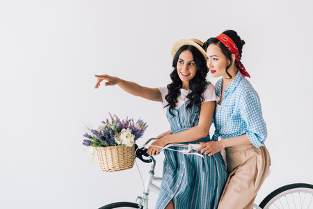 portrait of multicultural women in stylish retro clothing sitting on bicycle isolated on grey