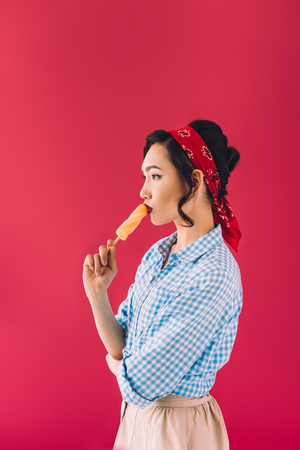 side view of stylish asian woman eating popsicle isolated on pink