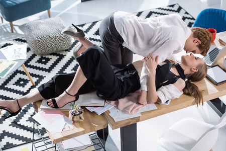 kissing lesbian couple of fashion designers lying on table