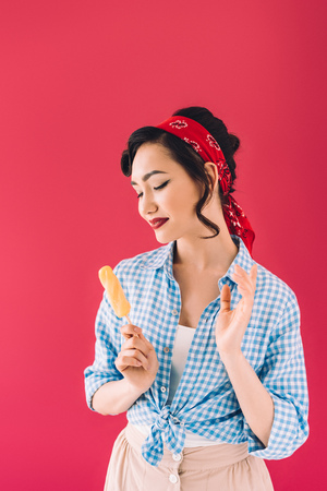 portrait of stylish smiling asian woman with popsicle isolated on pink