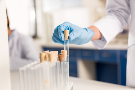 partial view of scientist working with test tubes, laboratory researcher concept