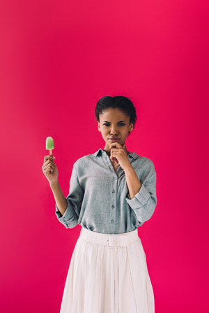 portrait of pensive african american woman with popsicle in hand isolated on pink