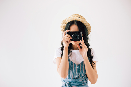 obscured view of woman taking picture on photo camera isolated on grey