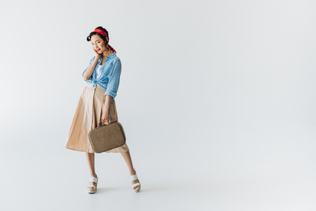 smiling stylish asian woman with suitcase in hand looking at camera isolated on grey Фото со стока
