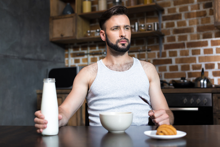 handsome young man pouring milk from bottle at breakfast Stok Fotoğraf