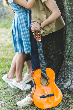 cropped shot of beautiful young couple with guitar in park Stock Photo