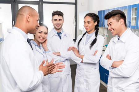 Team of young doctors in lab coats discussing work in laboratory