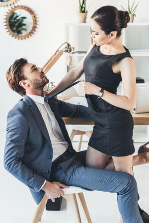 Mujer en vestido negro y tacones altos de pie sobre un hombre en traje sentado en una silla y tirando de él por la corbata