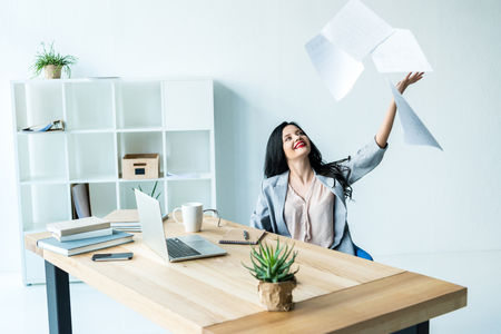 portrait of smiling businesswoman throwing documents away while sitting at workplace in office