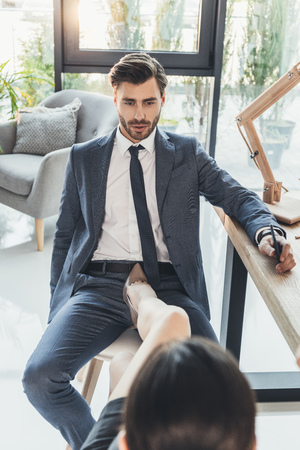 Woman in high heels placing her foot on a chair between legs of young man in business suit Standard-Bild