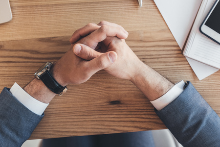 Cropped shot of male hands clasped together on wooden desk