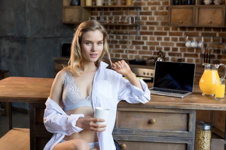 Jeune femme sensuelle en lingerie ayant son café du matin dans la cuisine Banque d'images