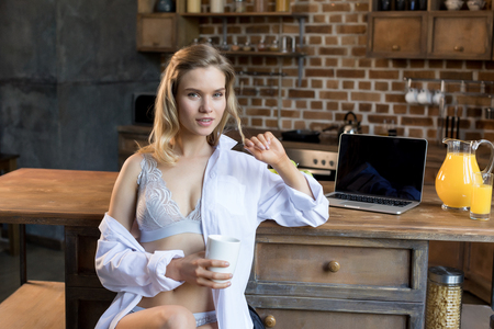 Young sensual woman in lingerie having her morning coffee in kitchen  Stok Fotoğraf