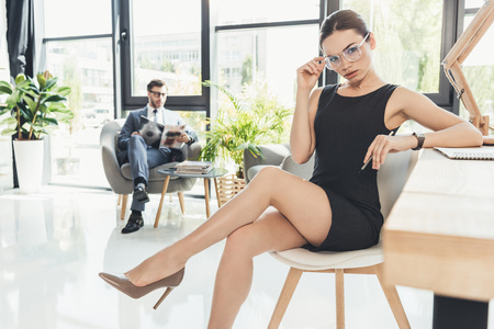 Young businesswoman in black dress and glasses sitting in a chair at office with legs crossed Stockfoto