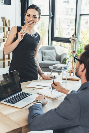 Young businesswoman in black dress standing over desk and smiling flirtatiously at her boss