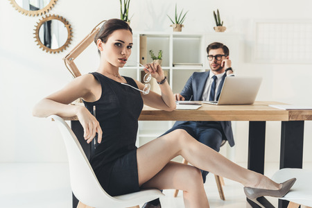 Young businesswoman sitting seductively on a chair in office with glasses in her hand