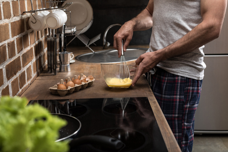 partial view of young man preparing eggs for breakfast in kitchen at home Stock Photo