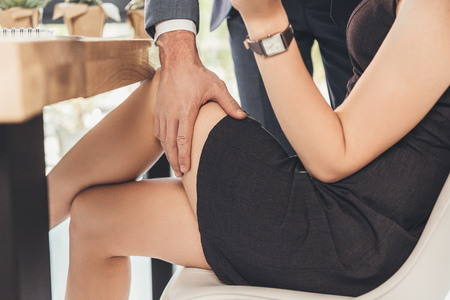 Cropped shot of a man in a suit groping woman in short black dress on a thigh