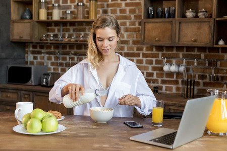 Young attractive blonde woman having corn flakes with milk for breakfast in kitchen  Stok Fotoğraf