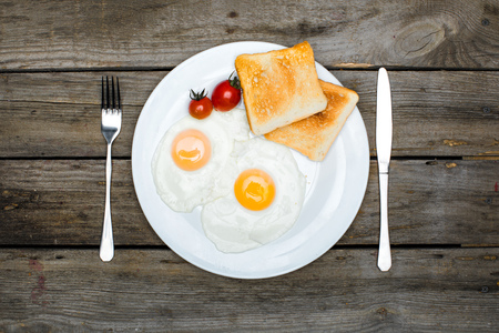 top view of fresh tasty breakfast with fried eggs and toasts on plate