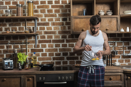 handsome bearded young man preparing eggs for breakfast in kitchen at home Stock Photo
