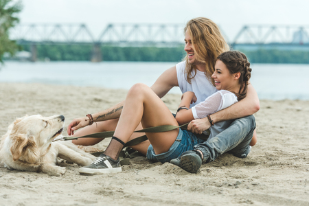 beautiful young couple with dog on beach