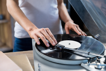 Cropped, close-up image of woman using vinyl audio player Stock Photo