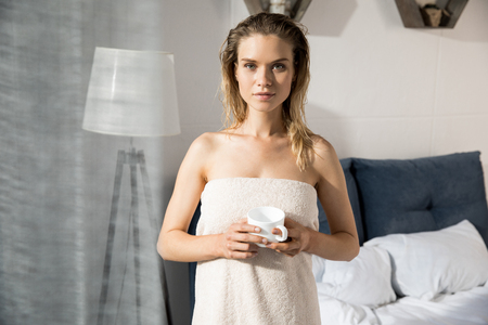 Young beautiful woman wrapped up with bath towel standing with coffee in bedroom