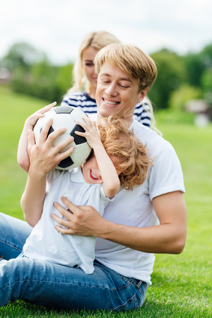 happy young family with one child playing with soccer ball on green lawn Stok Fotoğraf